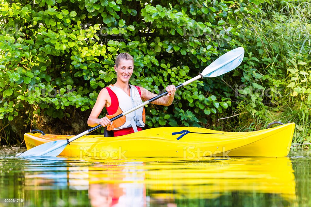 Woman driving with kayak on forest river stock photo