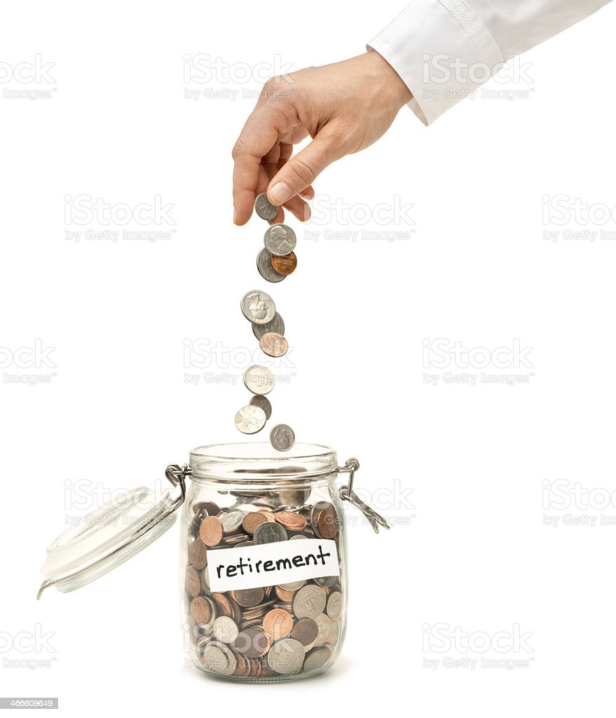 Woman Dropping Coins into Glass Jar Labeled Retirement stock photo