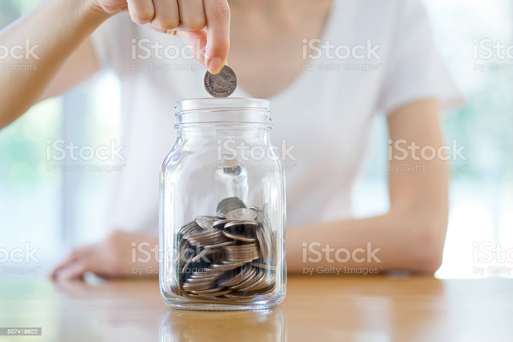 Woman Dropping Coins Into Glass Jar stock photo