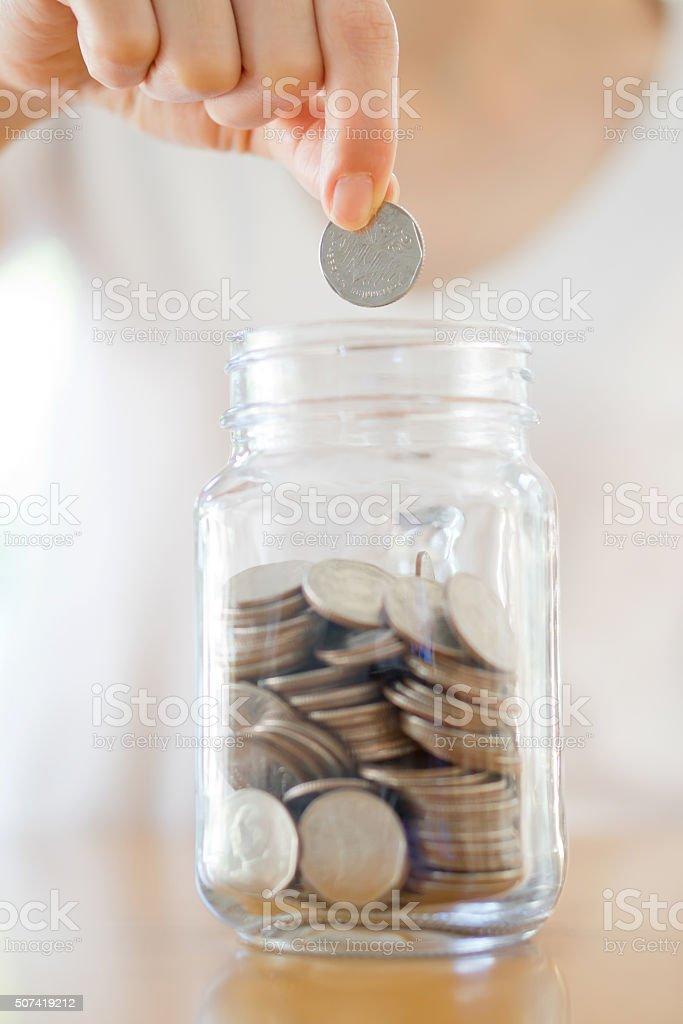 Frau Münzen fallen in ein Glas Glas – Foto