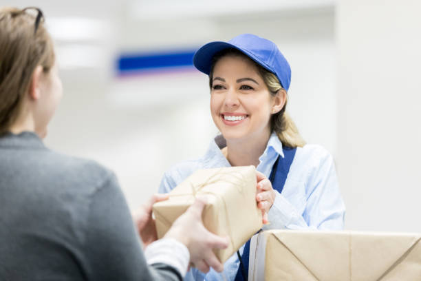 woman drops of packages at post office - postal worker стоковые фото и изображения