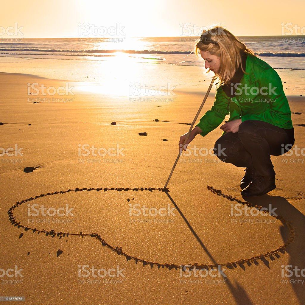 Frau drowing ein Herz-Form in den sand. Lizenzfreies stock-foto