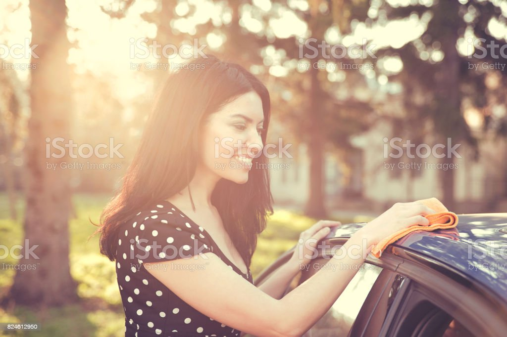 woman dry wiping her car with microfiber cloth after washing it stock photo