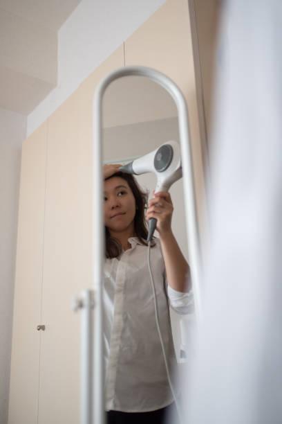 鏡の前で髪を乾燥させる女性 - 独身の若者 ストックフォトと画像