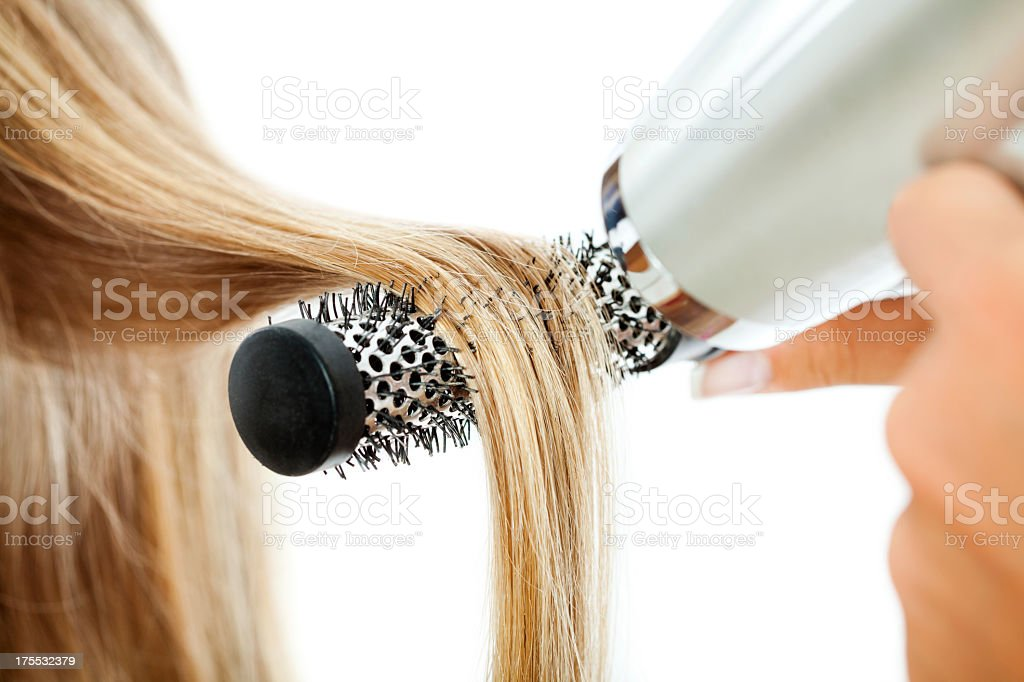 Woman drying hair with a hair dryer and brush stock photo