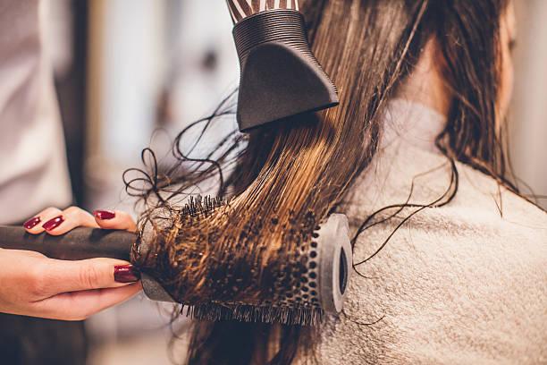 woman drying hair with a hair dryer and brush... - haarfön stock-fotos und bilder