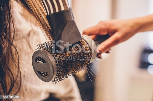 Woman drying hair with a hair dryer and brush