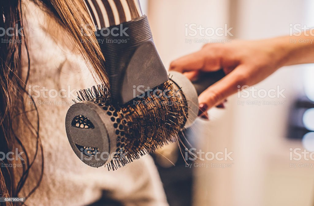 Woman drying hair with a hair dryer and brush... stock photo