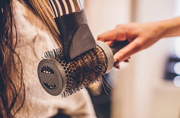 woman drying hair with a hair dryer and brush... - salão de beleza - fotografias e filmes do acervo