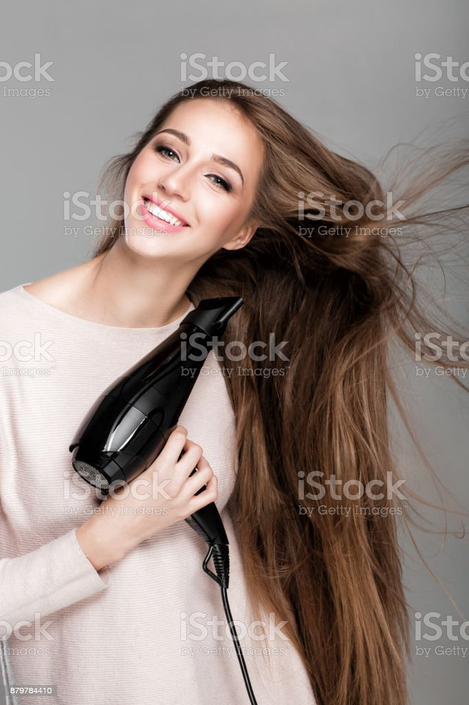 woman drying her hair with dryer stock photo