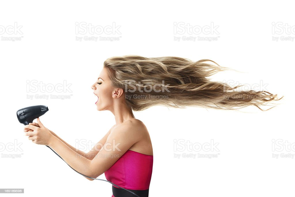 Woman drying long hair with electric fan stock photo