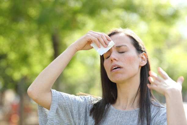 Woman drying sweat using a wipe in a warm summer day stock photo
