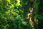 woman in her 40s doing a Canopy Tour Costa Rica, zip lines between trees.
