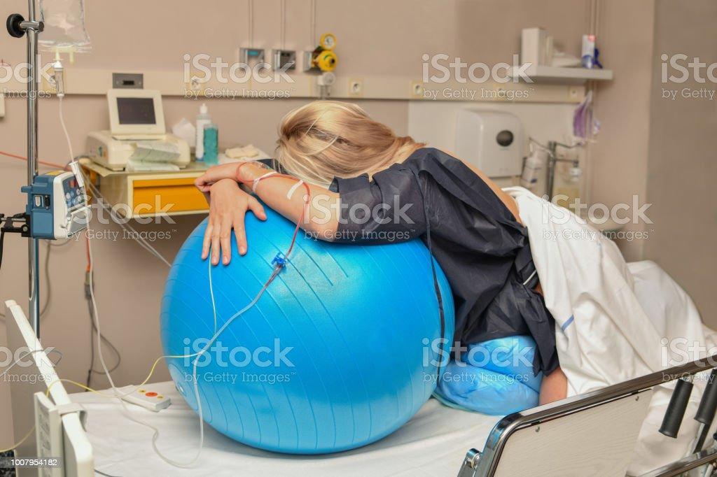 Mujer durante las contracciones en una bola de la aptitud hospital de parto foto de stock libre de derechos