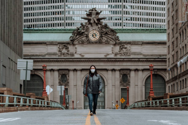 NYC woman during COVID-19 wearing mask on the street stock photo