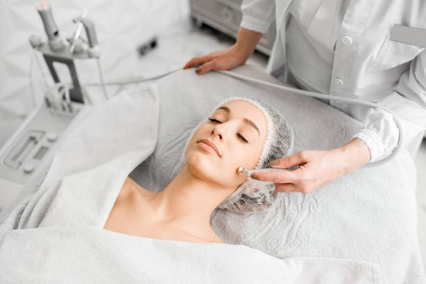 Woman during the facial treatment procedure Young woman during the facial treatment procedure in the cosmetology office peel plant part stock pictures, royalty-free photos & images