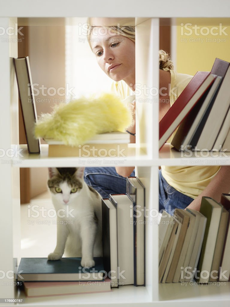 A woman dusting her book shelf stock photo