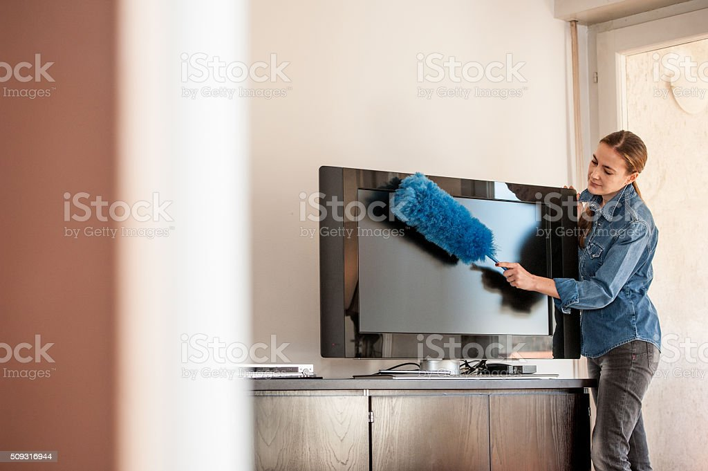 Woman Dusting Television, Copy Space stock photo