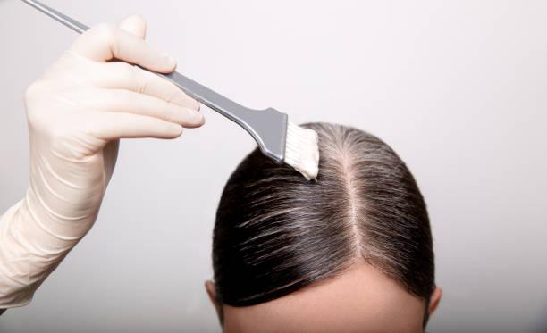 女性はブラシと髪の色で白髪の根を染める、クローズアップ - ごま塩 ストックフォトと画像