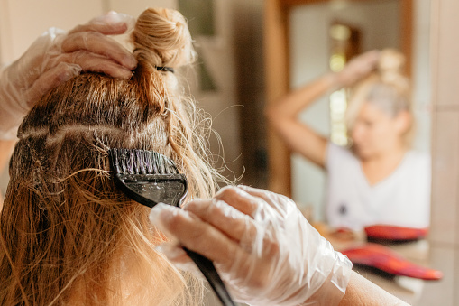 Rear view of woman dyeing hair in front of mirror at home