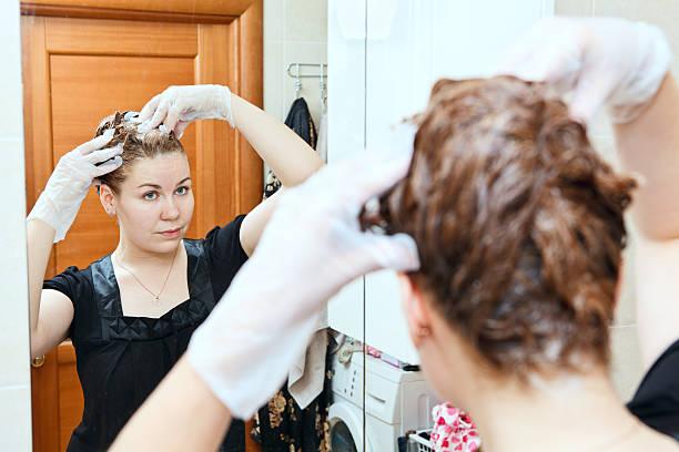 woman dyeing hairs at home - gekleurd haar stockfoto's en -beelden