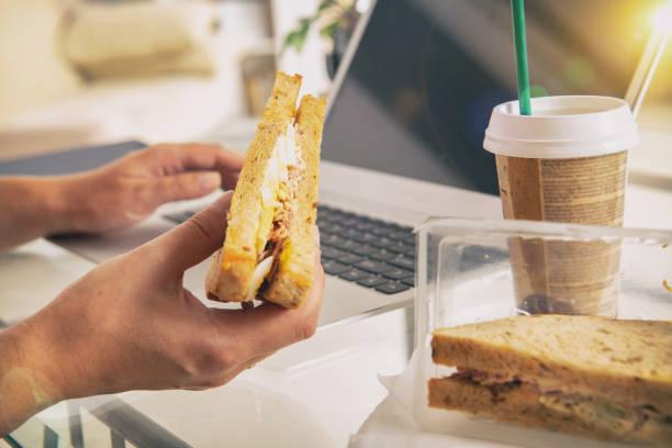 Frau, die ein Frühstück Sandwich zu essen, während der Arbeit mit einem laptop – Foto