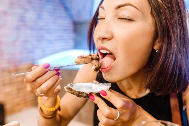 Frau isst eine Delikatessen-Auster, Nahaufnahme in einem Restaurant – Foto