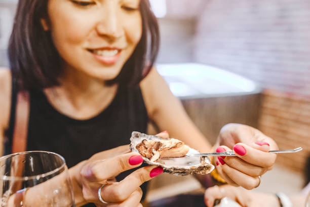 woman eating a delicacy oyster, close-up at a restaurant - oyster stock pictures, royalty-free photos & images