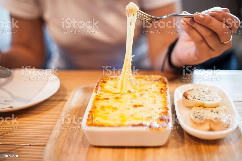 woman eating a delicious lasagna stock photo