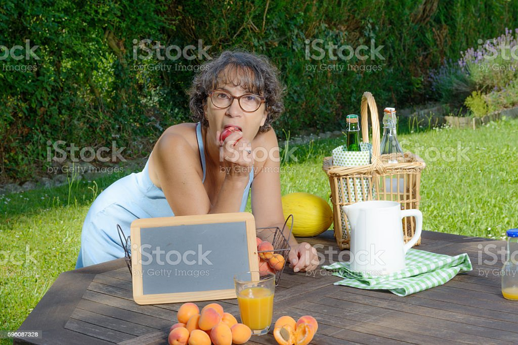 woman eating a fruit in his garden royalty-free stock photo