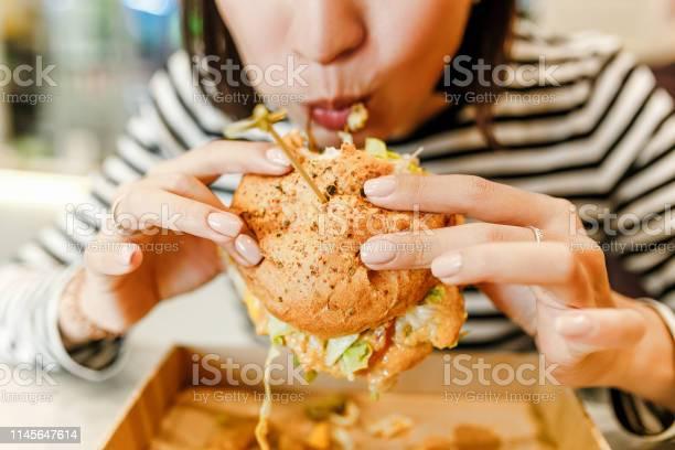 Woman eating a hamburger in modern fastfood cafe lunch concept picture id1145647614?b=1&k=6&m=1145647614&s=612x612&h=1ncpnwm9idqfgrdh msirjpixebvsamwuunyr0k1qt4=
