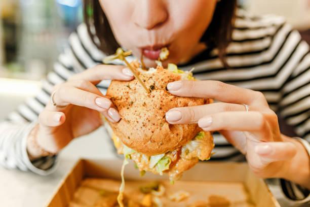 婦女吃漢堡包在現代速食咖啡館, 午餐概念 - 不健康飲食 個照片及圖片檔