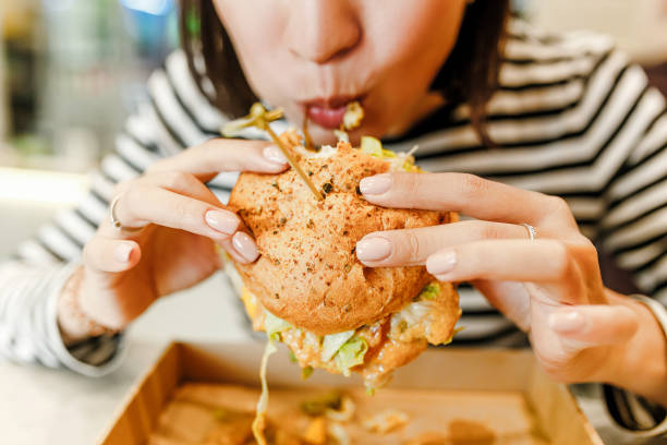 woman eating a hamburger in modern fastfood cafe, lunch concept - eating imagens e fotografias de stock