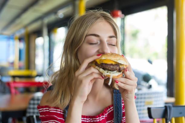 bir hamburger yiyen kadın - cheeseburger stok fotoğraflar ve resimler