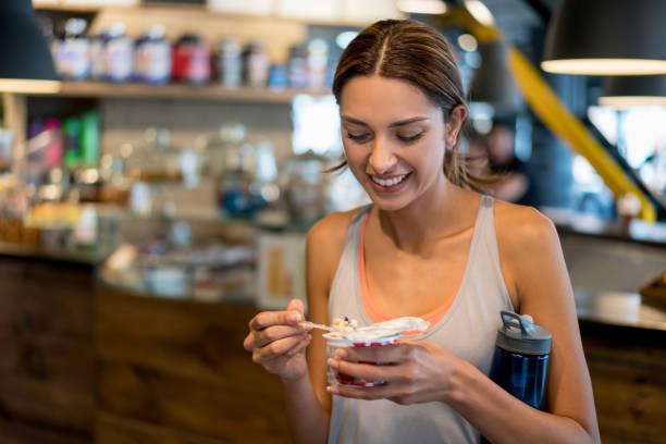 Mujer de comer una merienda saludable en el gimnasio - foto de stock