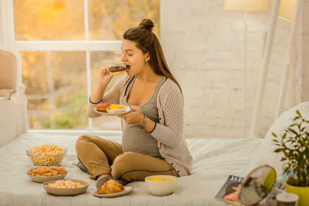 kvinna äta en massa godis medan graviditet - cravings bildbanksfoton och bilder