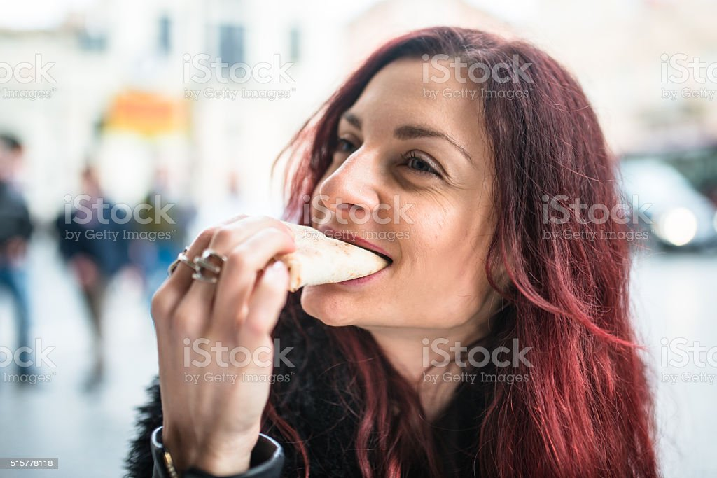 woman eating a pizza at restaurant stock photo