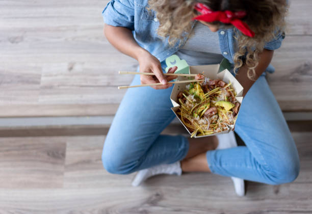 woman eating a poke bowl at home while moving house - food delivery imagens e fotografias de stock