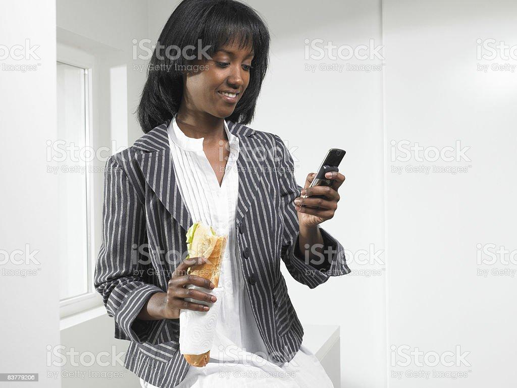 Mujer comer un sándwich en el teléfono Bruselas photo libre de droits