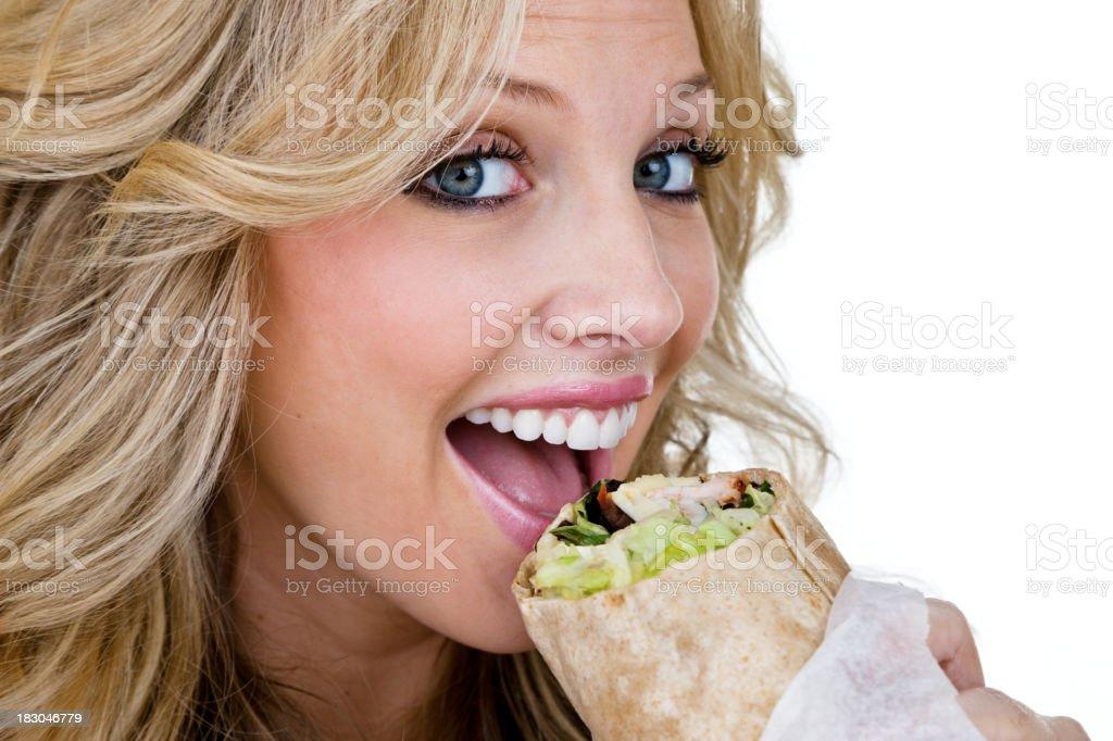 Woman eating a sandwich wrap royalty-free stock photo