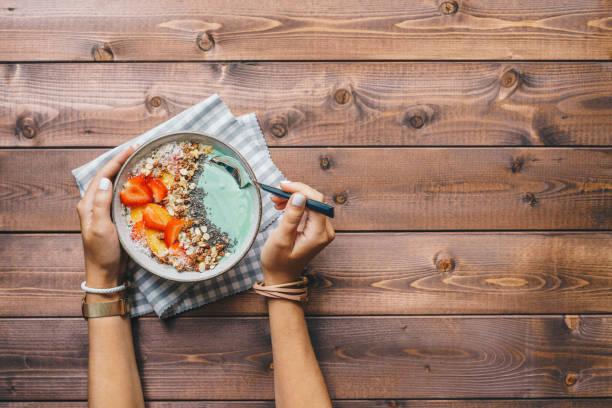 Frau isst eine Smoothie-Schüssel mit frischen Beeren, Müsli und Chia-Samen gekrönt – Foto