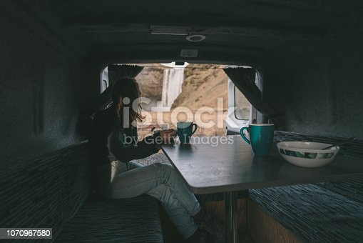 Young Caucasian woman eating and drinking tea and looking at Skogafoss  waterfall from camper van