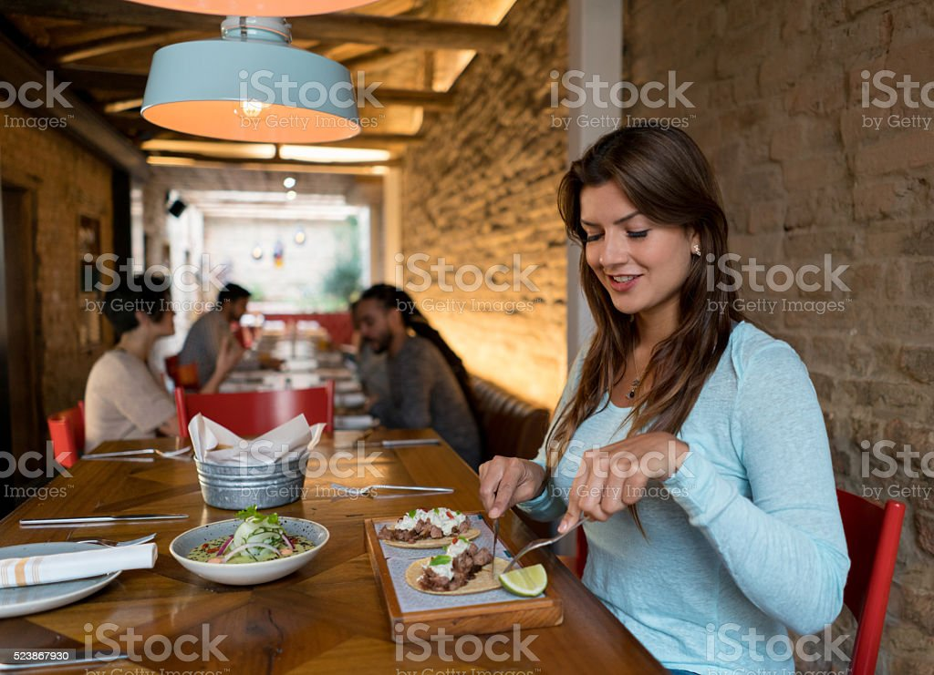 Woman eating at a Mexican restaurant stock photo