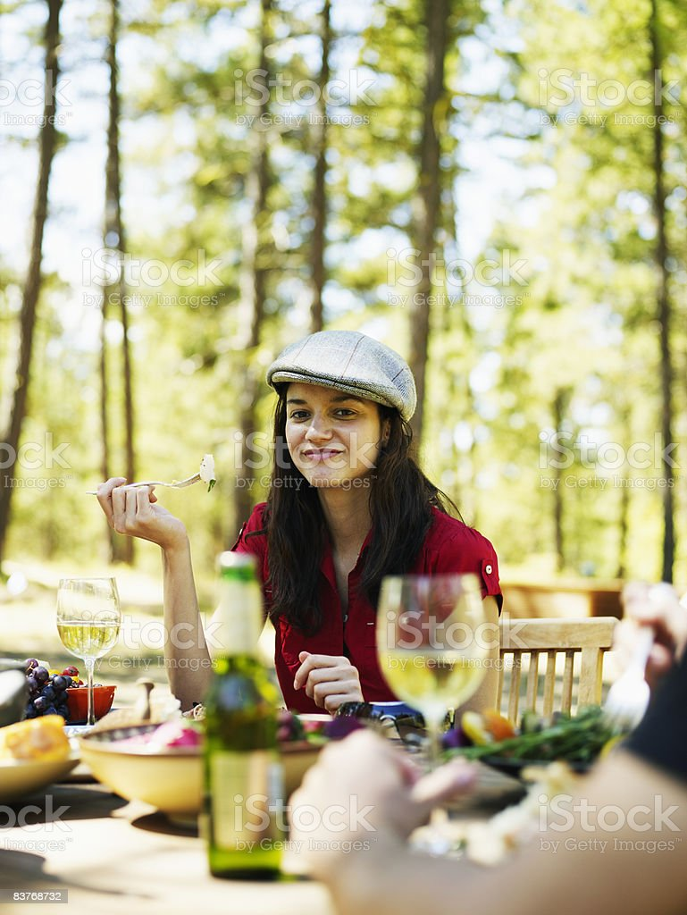 Woman eating at outdoor dining table foto stock royalty-free