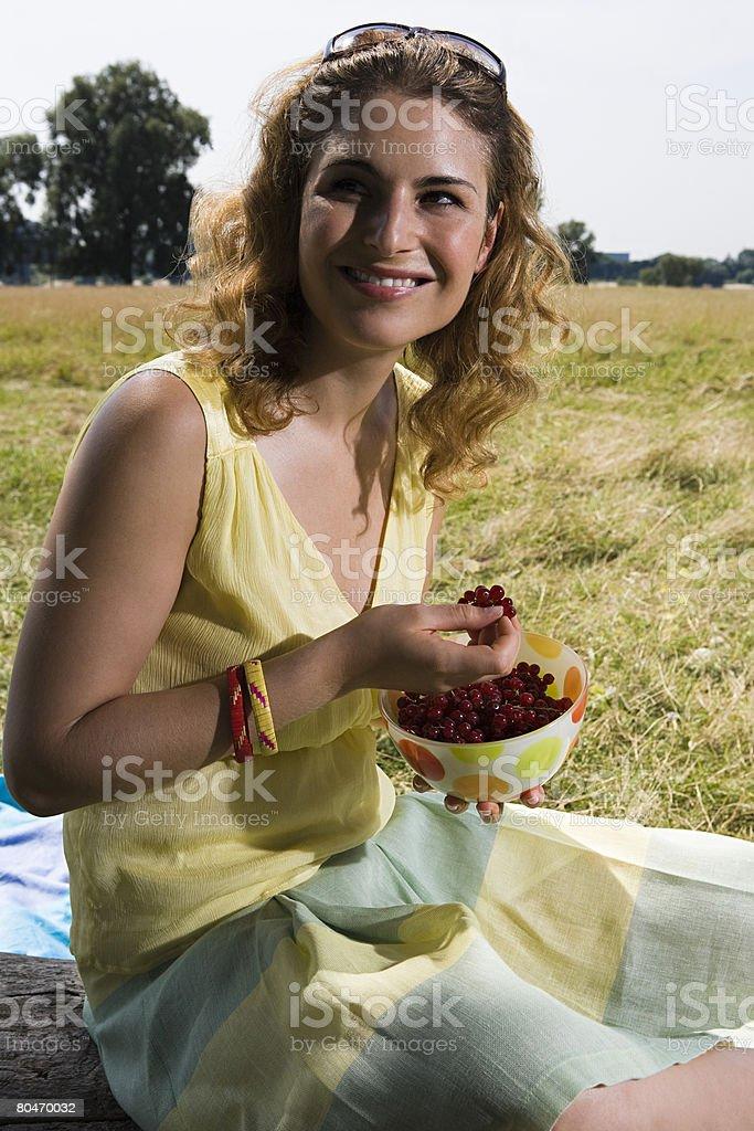 Mulher comer bagas em um campo foto de stock royalty-free