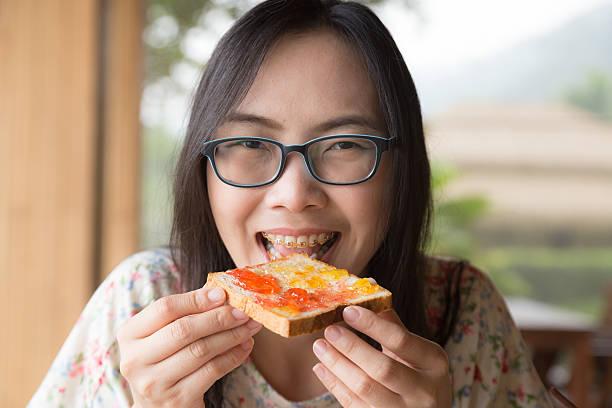 Frau isst Brot und Marmelade – Foto