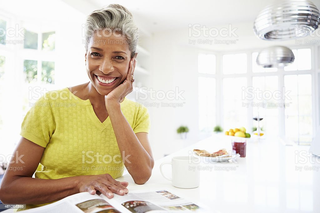 Woman Eating Breakfast And Reading Magazine stock photo