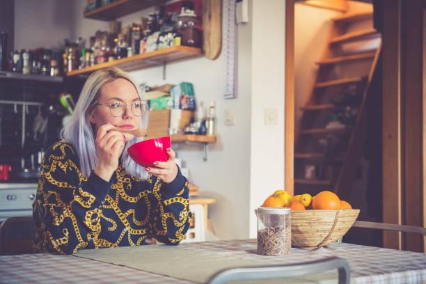 woman eating breakfast at home - showus стоковые фото и изображения