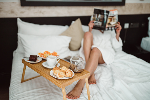 683349444 istock photo Woman eating breakfast in bed and reading a magazine 1265191066