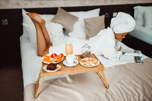 683349444 istock photo Woman eating breakfast in bed and reading a magazine 1265191067